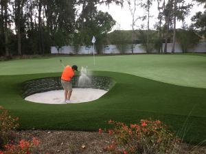 huge artificial grass golf green with guy shooting from stacked sod bunker