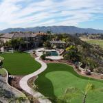 Aerial view of backyard artificial grass lawn and putting green