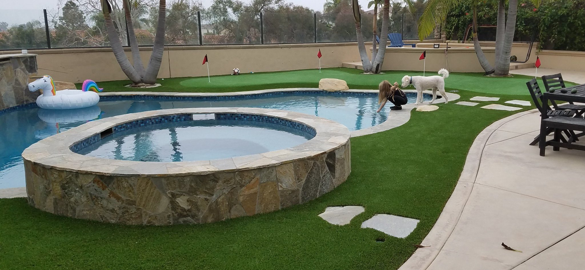backyard landscaping with artificial grass lawn and putting green