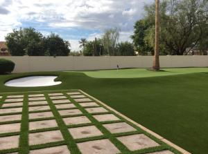 beautiful artificial grass backyard with pavers and putting green